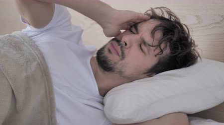 adversidade : Restless Man Having Headache While Sleeping On Bed