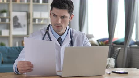 документация : Doctor Working on Medical Report and Laptop
