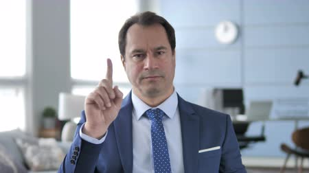 rejeitar : No, Middle Aged Businessman Rejecting Offer by Waving Finger