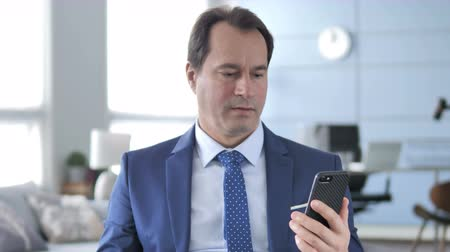 e mail address : Middle Aged Businessman Excited for Success while Using Smartphone Stock Footage