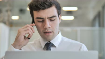 discar : Businessman Talking on the Phone and Working on the Laptop, Frontal View Stock Footage