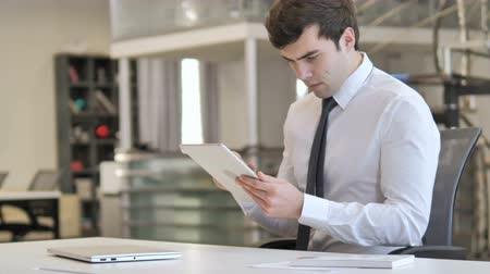 e mail address : Young Businessman Browsing Internet on Tablet Stock Footage