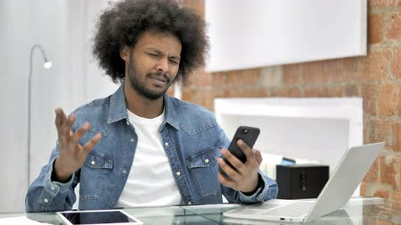 e mail address : African Man Reacting to Smart Phone in Loft Office
