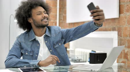 fotky : African Man Taking Selfie by Smartphone in Loft Office