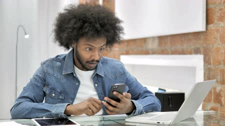 e mail address : African Man in Shock while Using Smartphone