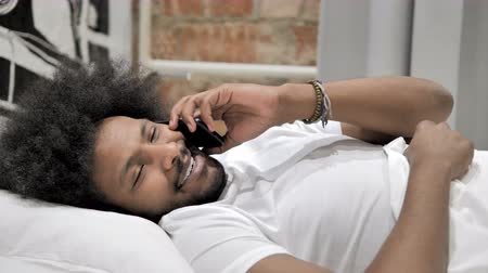discar : African Man Talking on Phone, lying in Bed