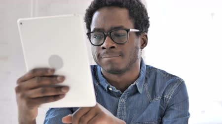 adresa : African Man Typing Email on Tablet