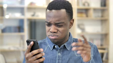 ashamed : African Man Reacting to Loss on Smartphone