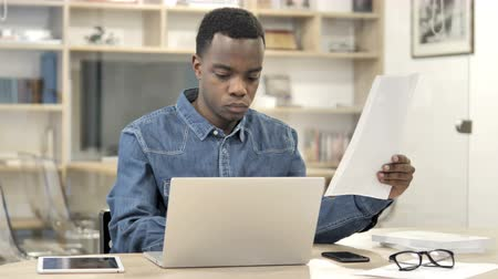 use laptop : African Man Doing Paperwork in Office