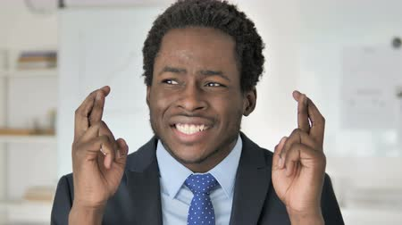 trabalhador de escritório : Fingers Crossed, African Businessman Wishing for Win Stock Footage