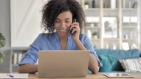 discar : African Woman Talking on Phone at Work Stock Footage
