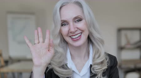 saying : Hello, Senior Businesswoman Waving Hand to Welcome