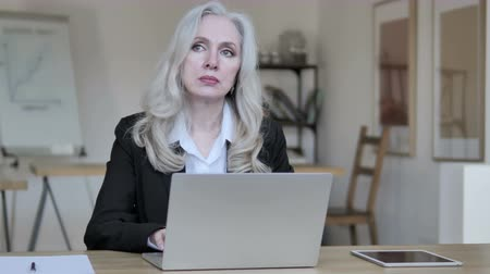 mentor : Senior Businesswoman Thinking and Working on Laptop Stock Footage