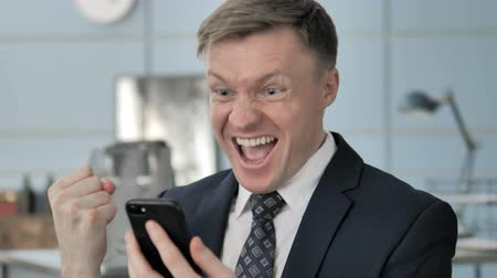winnings : Businessman Celebrating Success on Smartphone Stock Footage