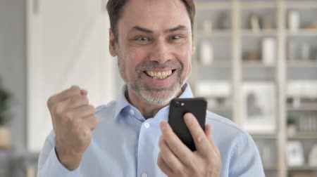 e mail address : Senior Aged Businessman Celebrating Success on Smartphone