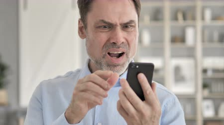 e mail address : Senior Aged Businessman Reacting While Using Smartphone Stock Footage