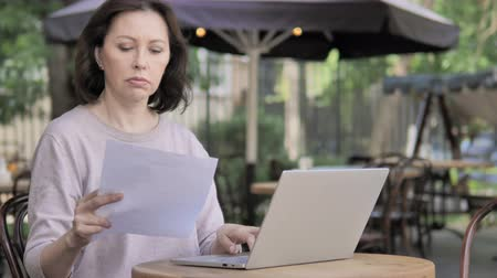 terra : Old Woman Sitting Outdoor doing paperwork Stock Footage