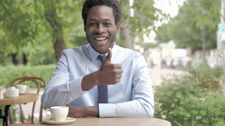 sikerül : Thumbs Up by African Businessman Sitting in Outdoor Cafe