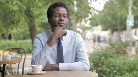 megvitatása : African Businessman Thinking While Sitting In Outdoor Cafe