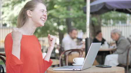 suceder : Young Woman Celebrating on Laptop Sitting in Cafe Terrace