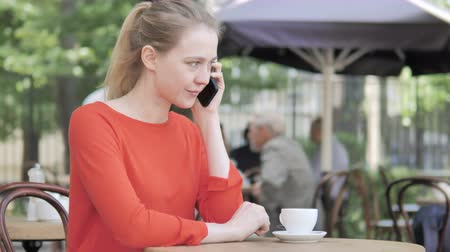 терраса : Young Woman Talking on Phone, Sitting in Cafe Terrace
