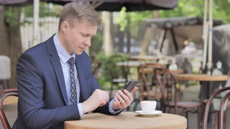 терраса : Businessman Celebrating Success on Phone, Sitting in Outdoor Cafe