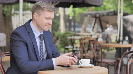 терраса : Businessman Using Smartphone Sitting in Outdoor Cafe Стоковые видеозаписи