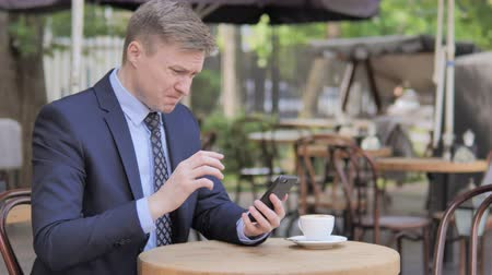 терраса : Businessman Upset by Loss on Smartphone, Sitting in Outdoor Cafe