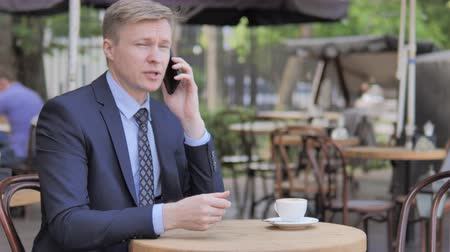 терраса : Businessman Talking on Phone while Sitting in Outdoor Cafe Стоковые видеозаписи