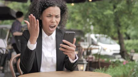 bizar : African Woman Upset by Loss on Smartphone, Sitting in Outdoor Cafe