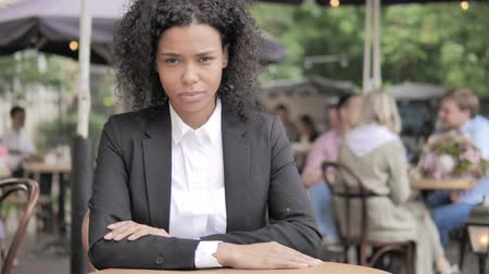 emin : Serious African Businesswoman Sitting in Outdoor Cafe