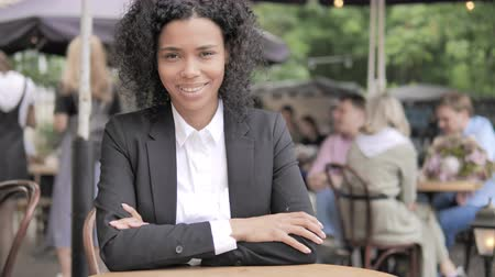 emin : Smiling African Businesswoman Sitting in Outdoor Cafe