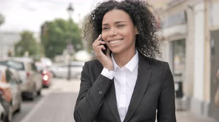 ascoltare : African businesswoman talking on phone
