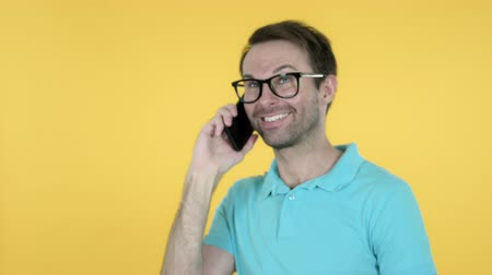 удовлетворения : Young Man Talking on Smartphone Isolated on Yellow Background