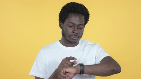 surfing the net : Young African Man Browsing Internet Using Smartwatch, Yellow Background