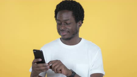 a böngésző : Young African Man Browsing Smartphone Isolated on Yellow Background Stock mozgókép