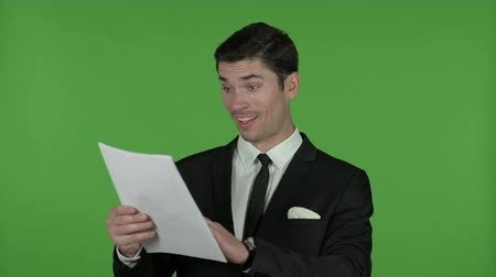 трейдер : Excited Young Businessman reading Documents, Chroma Key