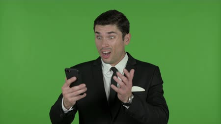 gritar : Young Businessman get Shocked on Cellphone, Chroma Key