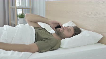 negotiations : Young Man talking on his Cellphone in Bed Stock Footage