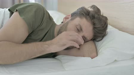 irritação : Close-up of Young Man having Headache in Bed while Sleeping