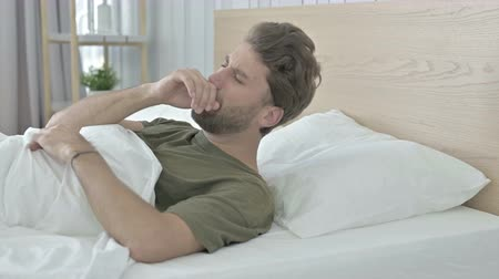 coughing : Sick Young Man coughing while having Nap in Bed Stock Footage