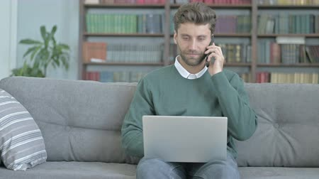 one man only : Young Man Smiling While Talking on Phone and Working on Laptop Stock Footage