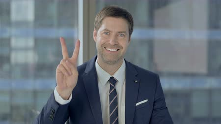трейдер : Cheerful Businessman Showing Victory Sign