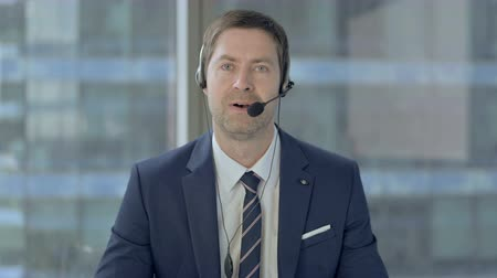 irodaház : Talking Middle Aged Businessman with Headset