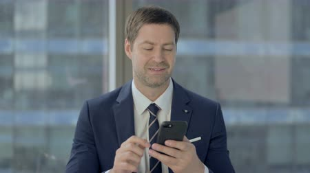 web sayfası : Businessman Scrolling Smartphone at Work Stok Video