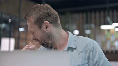 coughing : Close Up of Young Man Coughing at Work Stock Footage