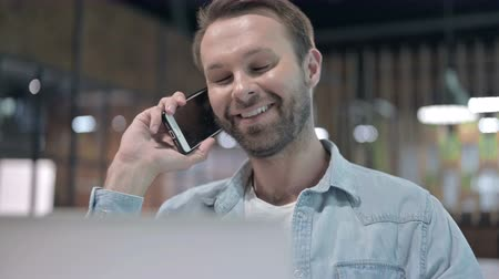 negotiate : Close Up of Positive Young Man Talking on Phone at Work