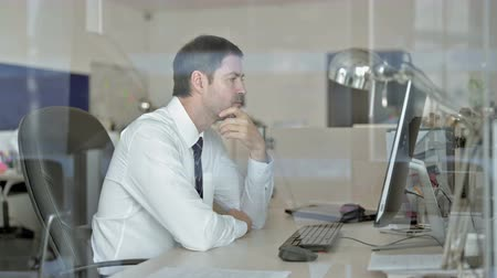 meia idade : Middle Aged Businessman Thinking and Looking at Computer Screen