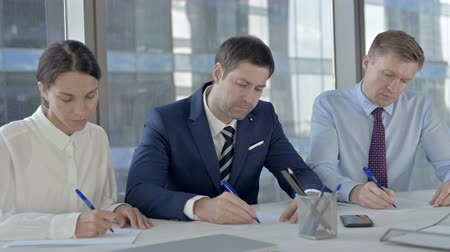 merging : Middle Aged Businessman Writing Documents with his Assistants on Office Table Stock Footage