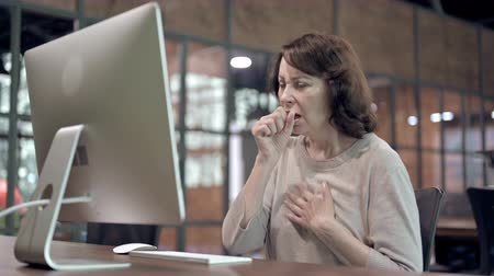 симптом : Sick Old Woman Coughing while Working on Computer
